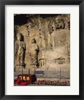 Buddha Statue in a Cave, Longmen Caves, Luoyang, China with Flowers Framed Print