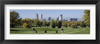 Framed Four people playing golf with buildings in the background, Denver, Colorado, USA