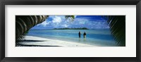 Framed Rear view of two native teenage girls in lagoon, framed by palm tree, Aitutaki, Cook Islands.