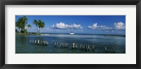 Framed Wooden posts in the sea with a boat in background, Laughing Bird Caye, Victoria Channel, Belize