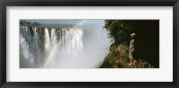 Framed Woman looking at a rainbow over the Victoria Falls, Zimbabwe