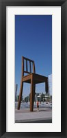 Framed Woman standing under a sculpture of large broken chair, Geneva, Switzerland