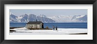 Framed Two hikers standing on the beach near a hunting cabin, Bellsund, Spitsbergen, Svalbard Islands, Norway