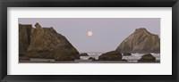Framed Sea stacks and setting moon at dawn, Bandon Beach, Oregon, USA