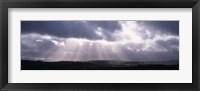 Framed Sunbeams radiating through dark clouds over rolling hills, Dartmoor, Devon, England