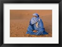 Framed Veiled Tuareg man sitting cross-legged on the sand, Erg Chebbi, Morocco