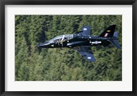 Framed Hawk T1 trainer aircraft of the Royal Air Force flying over a forest in North Wales