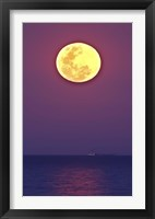 Framed Thunder's Moon and its reflection above the water