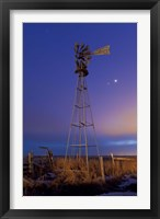 Framed Venus and Jupiter are visible behind an old farm water pump windmill, Alberta, Canada