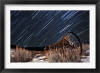 Framed Abandoned farm equipment against a backdrop of star trails