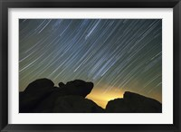 Framed Light pollution illuminates the sky and star tails above large boulders