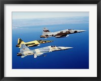 Framed Three F-5E Tiger II fighter aircraft in flight