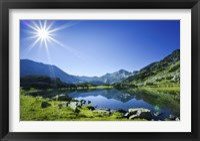 Framed Muratov Lake against blue sky and bright sun in Pirin National Park, Bulgaria