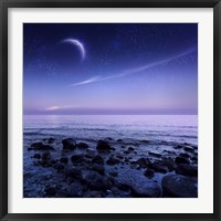 Framed Moon rising over rocky seaside against starry sky
