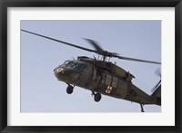 Framed UH-60 Blackhawk Medivac helicopter flies over Camp Warhorse
