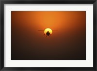 Framed AH-64D Apache Helicopter Flying into the Sun over Iraq