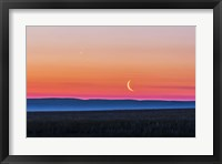 Framed Moon and Venus rising over the flat prairie horizon of Alberta, Canada