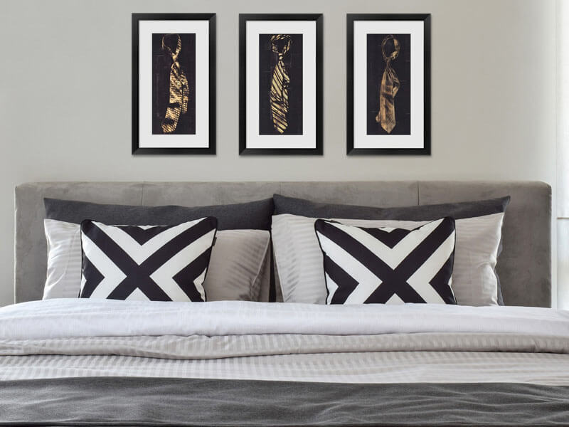 framed black and gold art over a bed