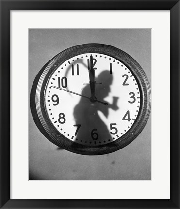 Framed Close-up of the shadow of a person carrying a scythe on a clock Print
