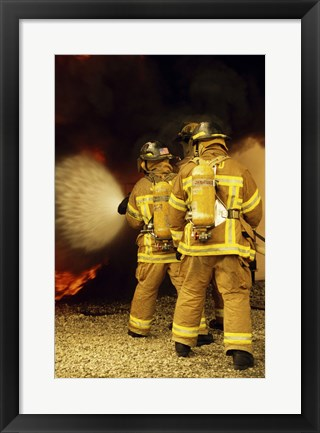 Framed Rear view of three firefighters extinguishing a fire Print