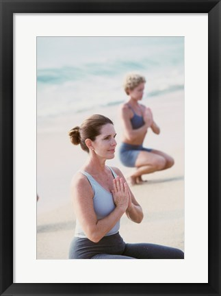Framed Young woman and a mid adult woman meditating on the beach Print