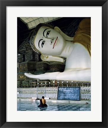 Framed Monk Sitting in Front of a Buddha Statue Print