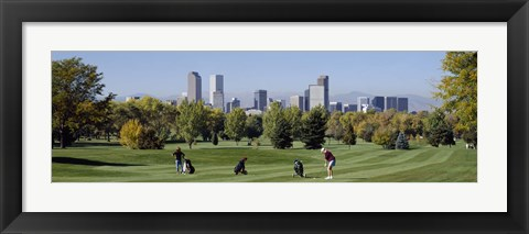 Framed Four people playing golf with buildings in the background, Denver, Colorado, USA Print