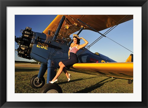 Framed 1940's style pin-up girl sitting on the wing of a Stearman biplane Print