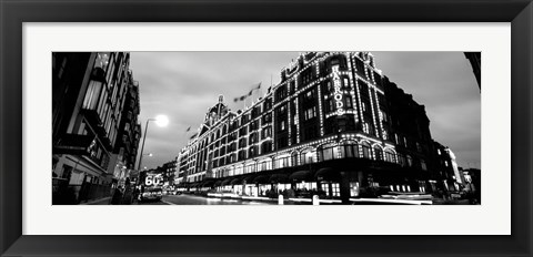 Framed Low angle view of buildings lit up at night, Harrods, London, England Print