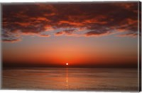 Framed layer of clouds is lit by the rising sun over Rio de la Plata, Buenos Aires, Argentina