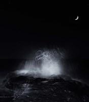 Framed crescent moon and waves splashing over rocks in Miramar, Argentina