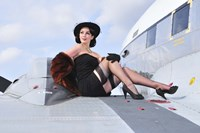 Framed Glamorous woman in 1940's style attire sitting on a vintage aircraft