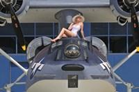 Framed Retro pin-up girl posing with a World War II era PBY Catalina seaplane