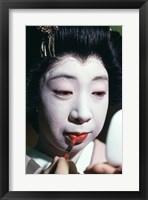 Framed Close-up of a geisha applying lipstick to her lips