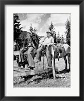 Framed Teenage cowboys sitting on rail fence