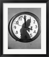 Framed Close-up of the shadow of a person carrying a scythe on a clock