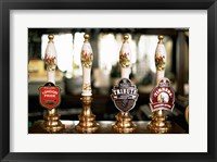 Framed Close-up of beer tap handles in a bar, London, England