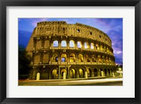 Low angle view of the old ruins of an amphitheater lit up at dusk, Colosseum, Rome, Italy Framed Print