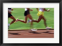 Framed Low section view of male athletes running on a running track