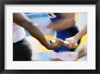 Framed Mid section view of runners exchanging baton at a relay race