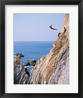Framed Male cliff diver jumping off a cliff, La Quebrada, Acapulco, Mexico