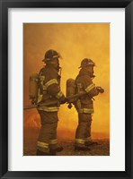 Framed Rear view of two firefighters extinguishing a fire