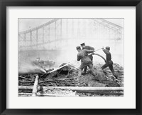 Framed Three firefighters extinguishing a fire