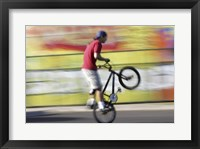 Side profile of a teenage boy performing a stunt on a bicycle Framed Print