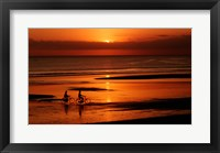 Framed Silhouette of a young couple cycling on the beach