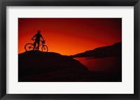 Framed red Silhouette of a man standing with his mountain bike, Lake Powell