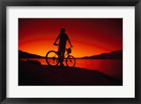 Silhouette of a man standing with a bike, Lake Powell, Utah Framed Print