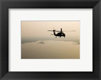 An Air Force helicopter flys over Lake Pontchatrain to New Orleans Framed Print