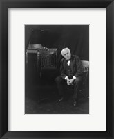 Framed Thomas Edison, seated beside phonograph
