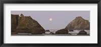 Framed Sea stacks and setting moon at dawn, Bandon Beach, Oregon, USA
